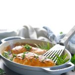 Oven baked boneless skinless chicken breast recipe in a gray baking dish