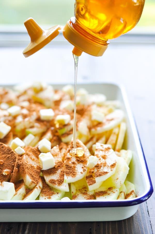 Drizzling honey over sliced apples