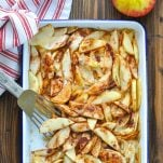 Long overhead shot of sliced baked apples on a baking sheet