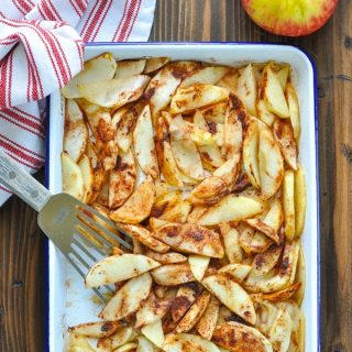 Long overhead shot of sliced baked apples on a baking sheet