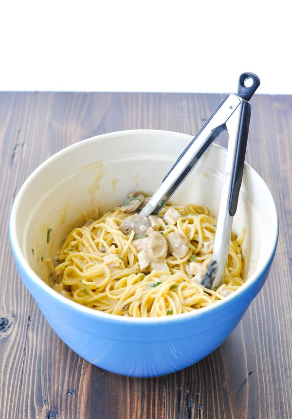 Mixing chicken tetrazzini in a large blue bowl
