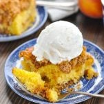 Close up shot of peach cake topped with a scoop of vanilla ice cream