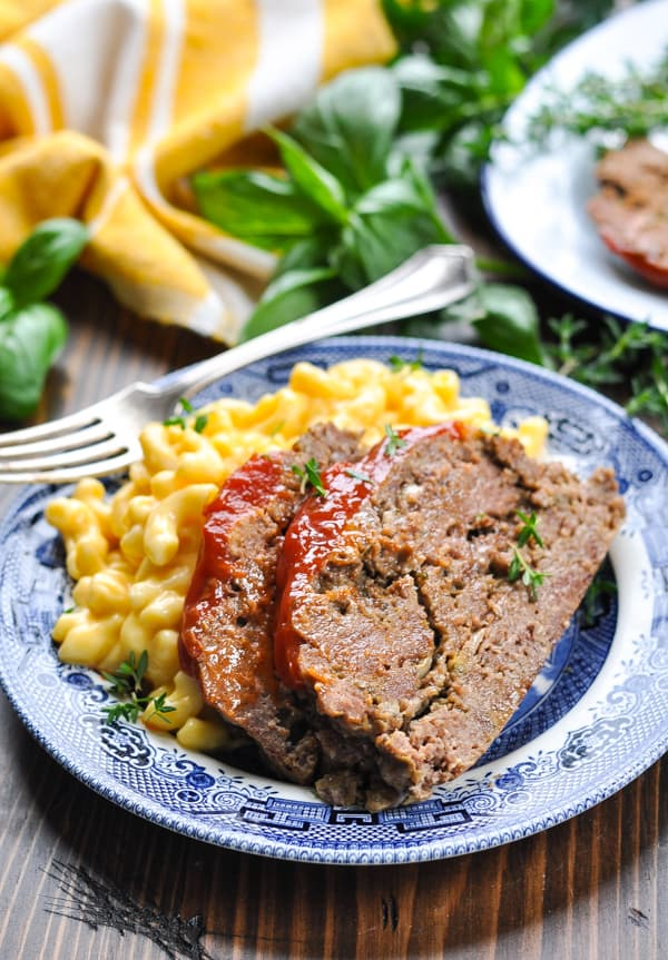 Close up shot of meatloaf on a plate with mac and cheese and fresh herbs