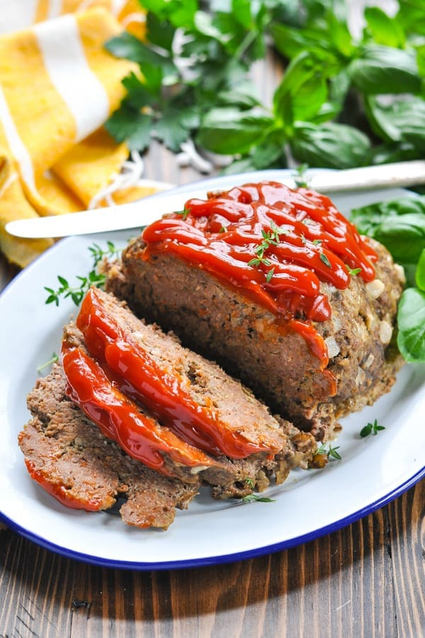 Sliced crock pot meatloaf garnished with herbs and covered in ketchup