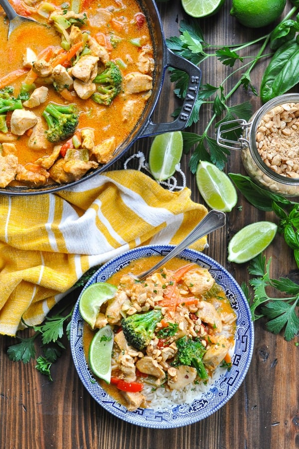 Thai chicken curry in a bowl with crushed peanuts and lime wedges on top