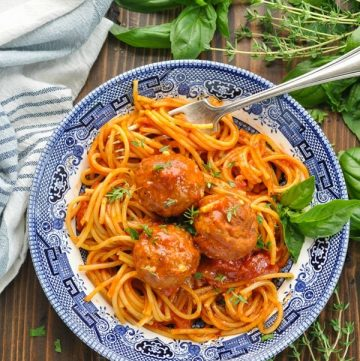 Close overhead shot of spaghetti and meatballs in a bowl garnished with fresh basil