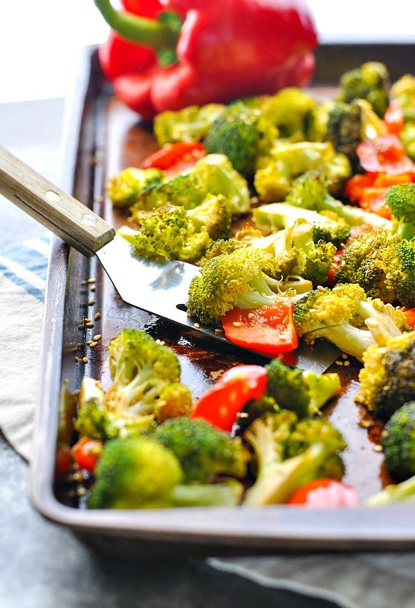 Oven roasted broccoli with red bell pepper on a baking sheet