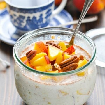 Glass bowl full of overnight refrigerator oatmeal with peaches and pecans
