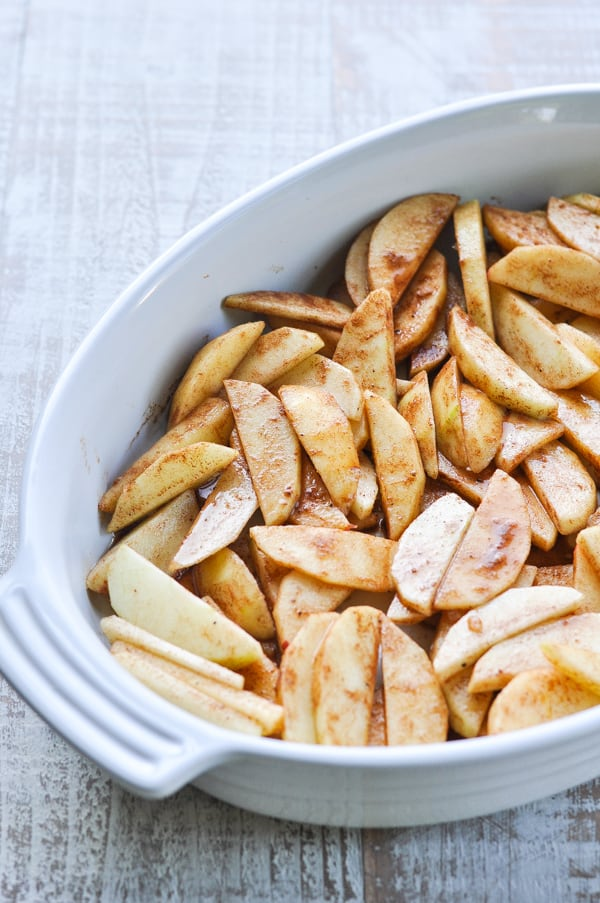Sliced apples with spices in a white baking dish
