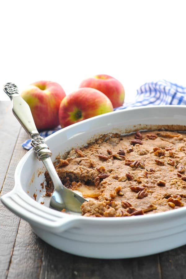 Easy apple dump cake in white baking dish with toasted pecans on top