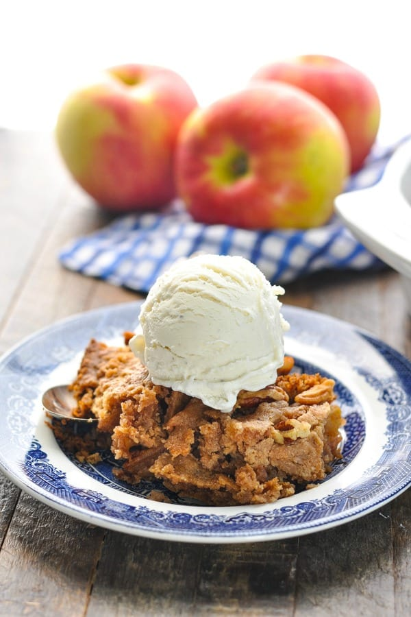 Close up shot of apple dump cake on a plate with vanilla ice cream on top