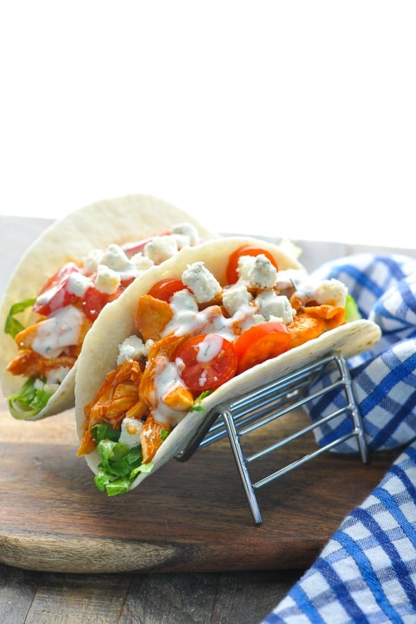 Two buffalo chicken wraps topped with blue cheese in a taco holder