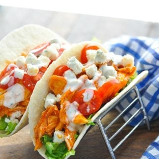 Buffalo chicken with lettuce and tomato in wraps on a wooden surface