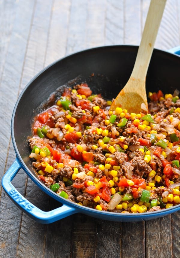 Ground beef mixture with tomatoes and corn in cast iron skillet