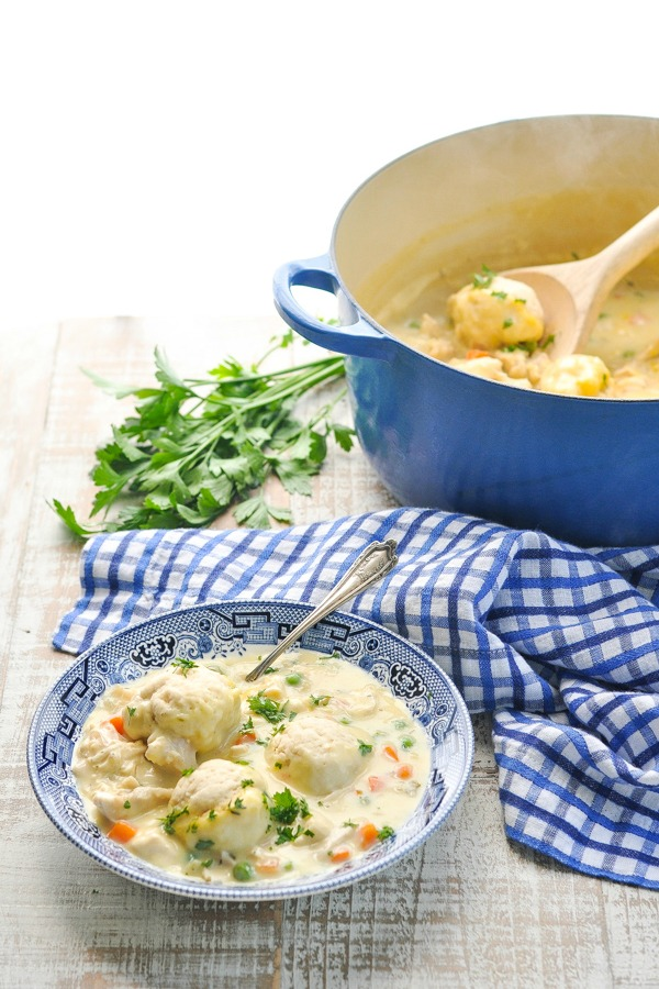Blue and white bowl with chicken and bisquick dumplings garnished with parsley