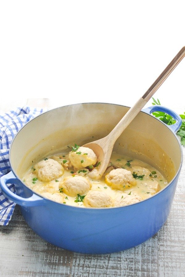 Front shot of Bisquick Dumplings in a blue Dutch oven with wooden serving spoon