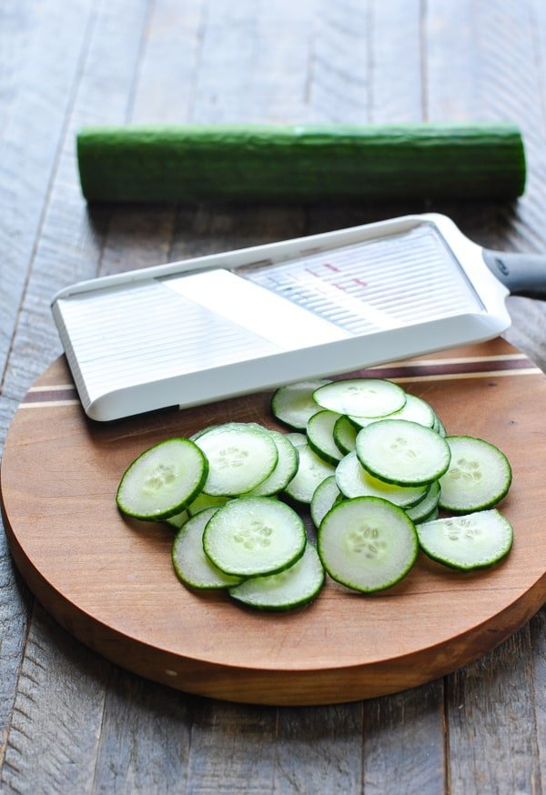 Thinly sliced cucumbers with mandoline on cutting board
