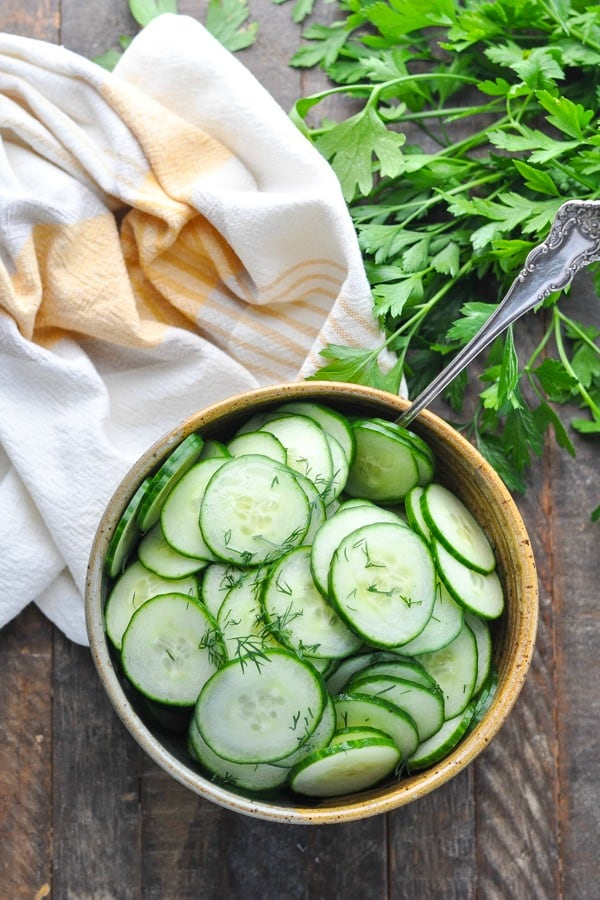 Overhead shot of bowl of cucumber salad with vinegar and a serving spoon
