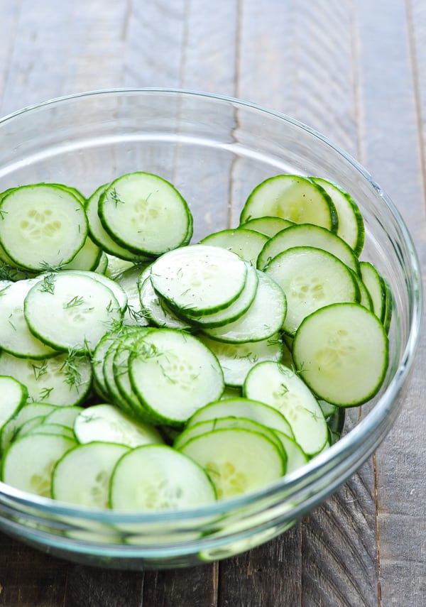 Sliced cucumbers with vinegar in a glass mixing bowl