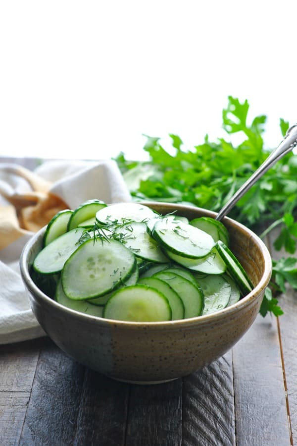 Bowl of the best cucumber salad with fresh parsley in the background