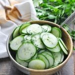 Close up shot of marinated cucumbers in a serving bowl garnished with fresh dill