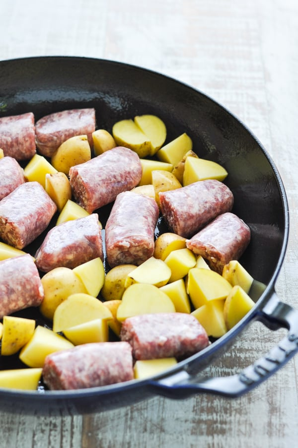 Bratwurst and potatoes in a cast iron skillet