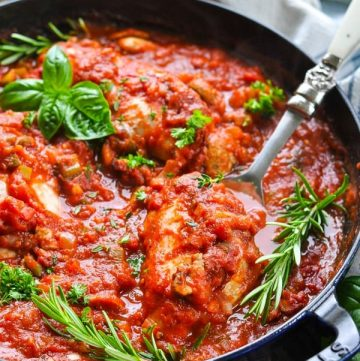 Chicken cacciatore in a cast iron skillet with a serving spoon