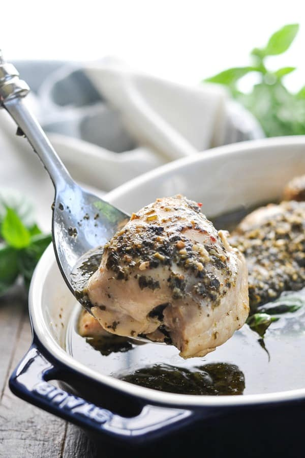 Baked pesto chicken thigh on serving spoon