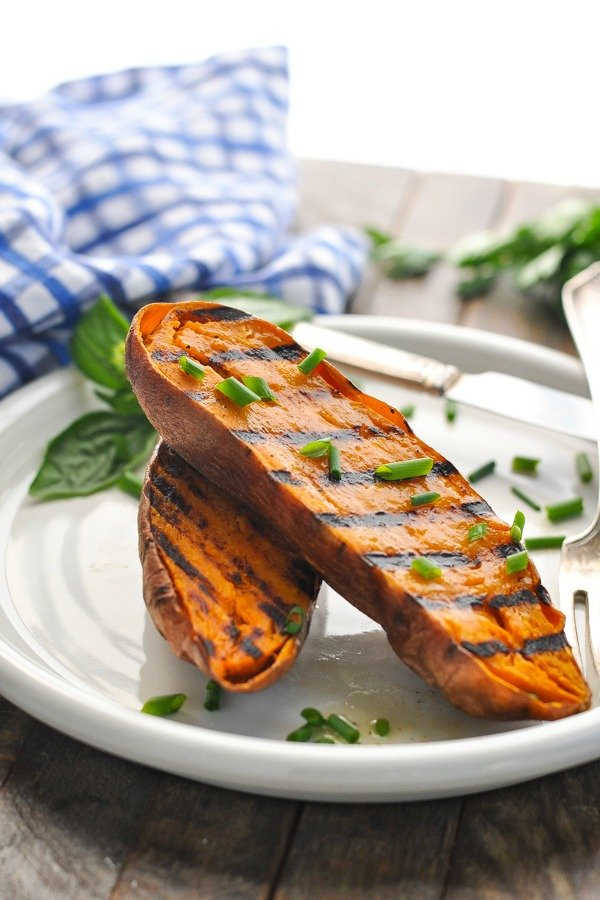Sweet potato with grill marks on a white plate with chives