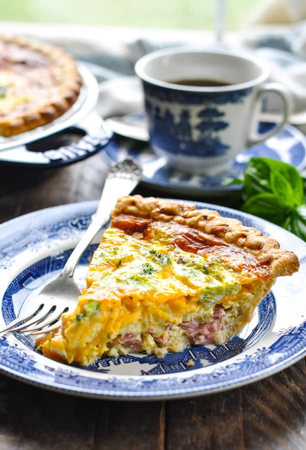 Slice of ham and cheese quiche with broccoli on a blue and white plate