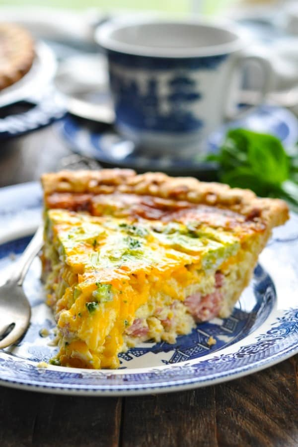 Close up front shot of ham cheddar and broccoli quiche on a plate