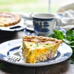 Front shot of a slice of ham cheese and broccoli quiche on blue and white plate