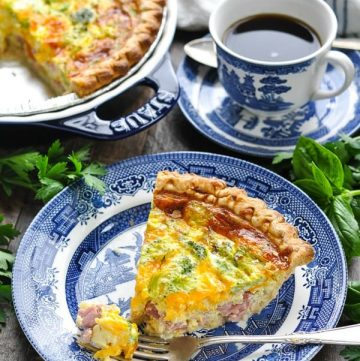 Photo of slice of ham cheddar and broccoli quiche on a plate with a bite on a fork