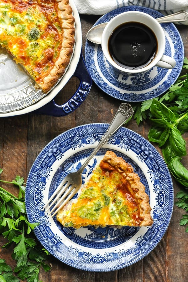 Long overhead shot of slice of broccoli and cheese quiche on a plate with coffee nearby