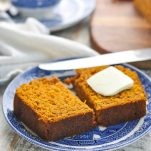 Slice of pumpkin bread recipe on a blue and white plate with a pat of butter on top
