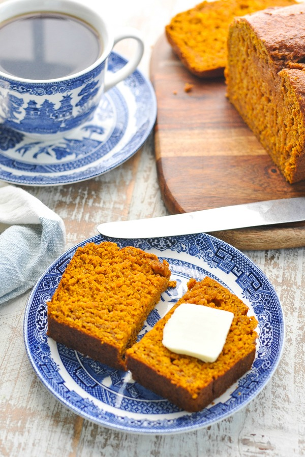 Overhead shot of pumpkin bread on a plate with butter on top