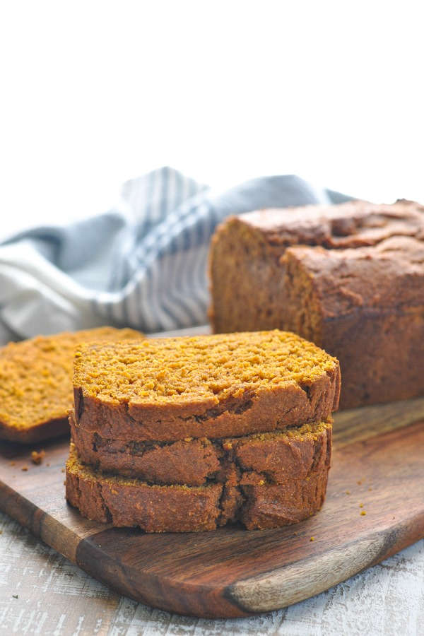 A stack of three slices of pumpkin bread on a wooden board
