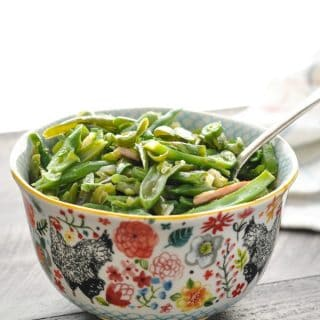A bowl of slow cooker southern green beans with bacon on a wooden surface