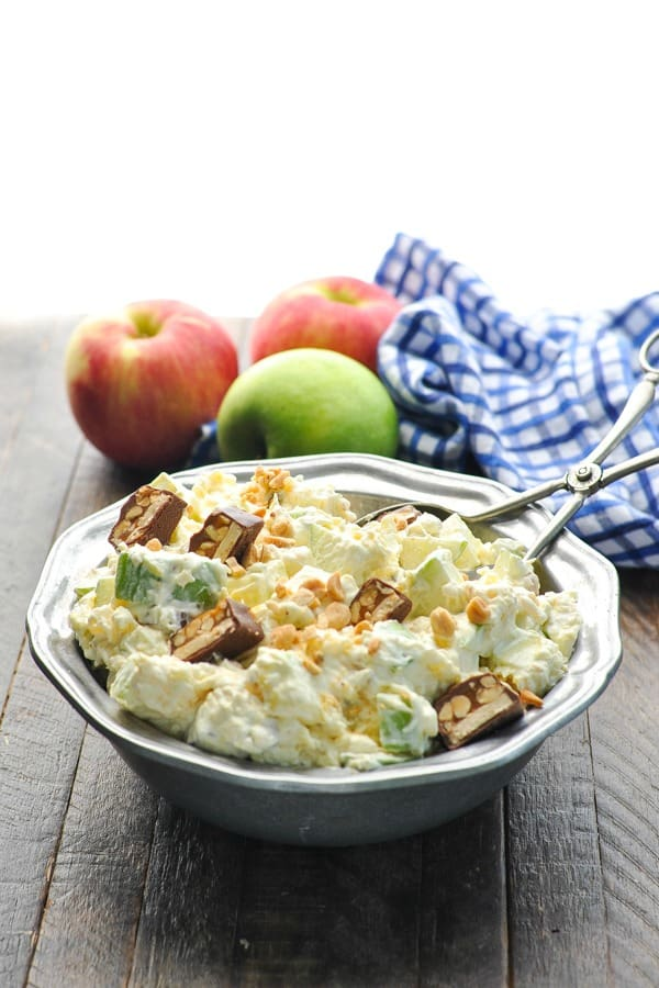 Front shot of bowl of Apple Fluff Snickers Salad on a table with fresh apples in background