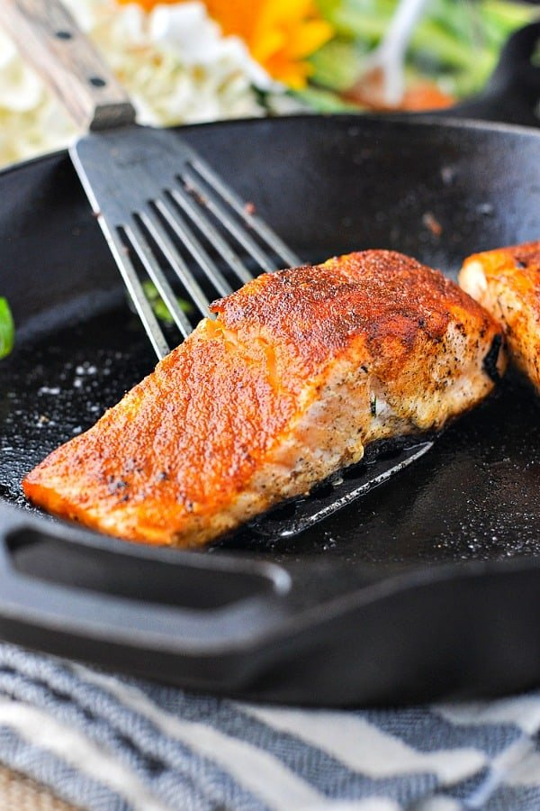 Blackened salmon in a cast iron skillet on a spatula