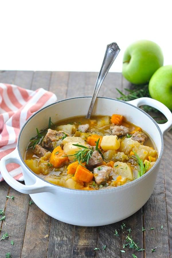Ladle in a white pot of pork stew