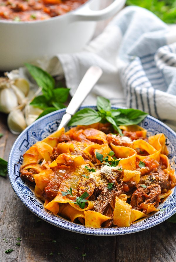 Close up front shot of beef ragu mixed with pappardelle pasta in a bowl