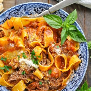 Close overhead shot of slow cooker beef ragu recipe served over pasta in a blue and white bowl
