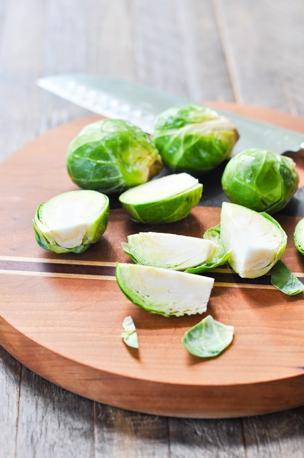 Demonstrating how to cut Brussels Sprouts on a cutting board