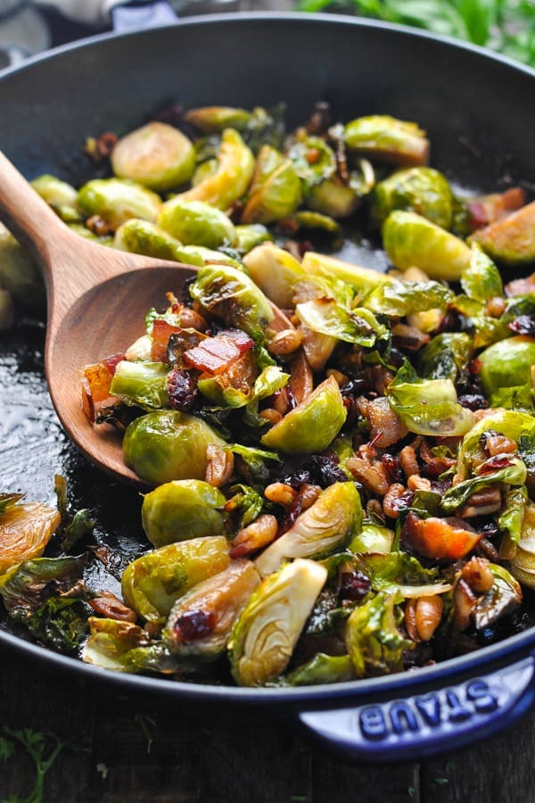 Close up shot of brussels sprouts with bacon on a wooden spoon
