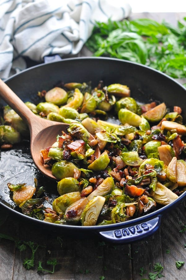 Wooden spoon in a skillet full of brussels sprouts with bacon and maple syrup
