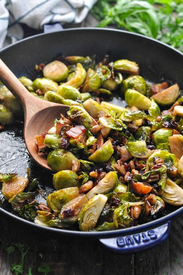 Close up shot of brussels sprouts in a pan with cranberries pecans and bacon