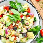Overhead shot of a bowl of chicken and tortellini salad with fresh vegetables and herbs