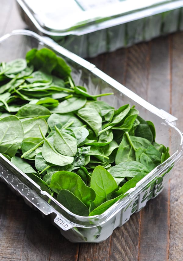 Container of fresh baby spinach leaves