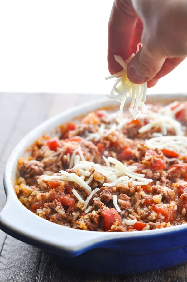 Sprinkling cheese on top of ground beef casserole